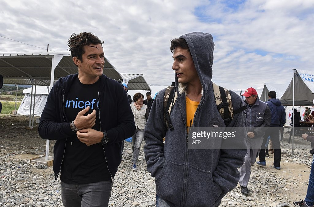 British actor and UNICEF Goodwill Ambassador Orlando Bloom (L) speaks with a Syrian refugee from Damascus Tarek Merry during his visit at the refugee registration camp near Gevgelija on September 28, 2015. AFP PHOTO / ARMEND NIMANI