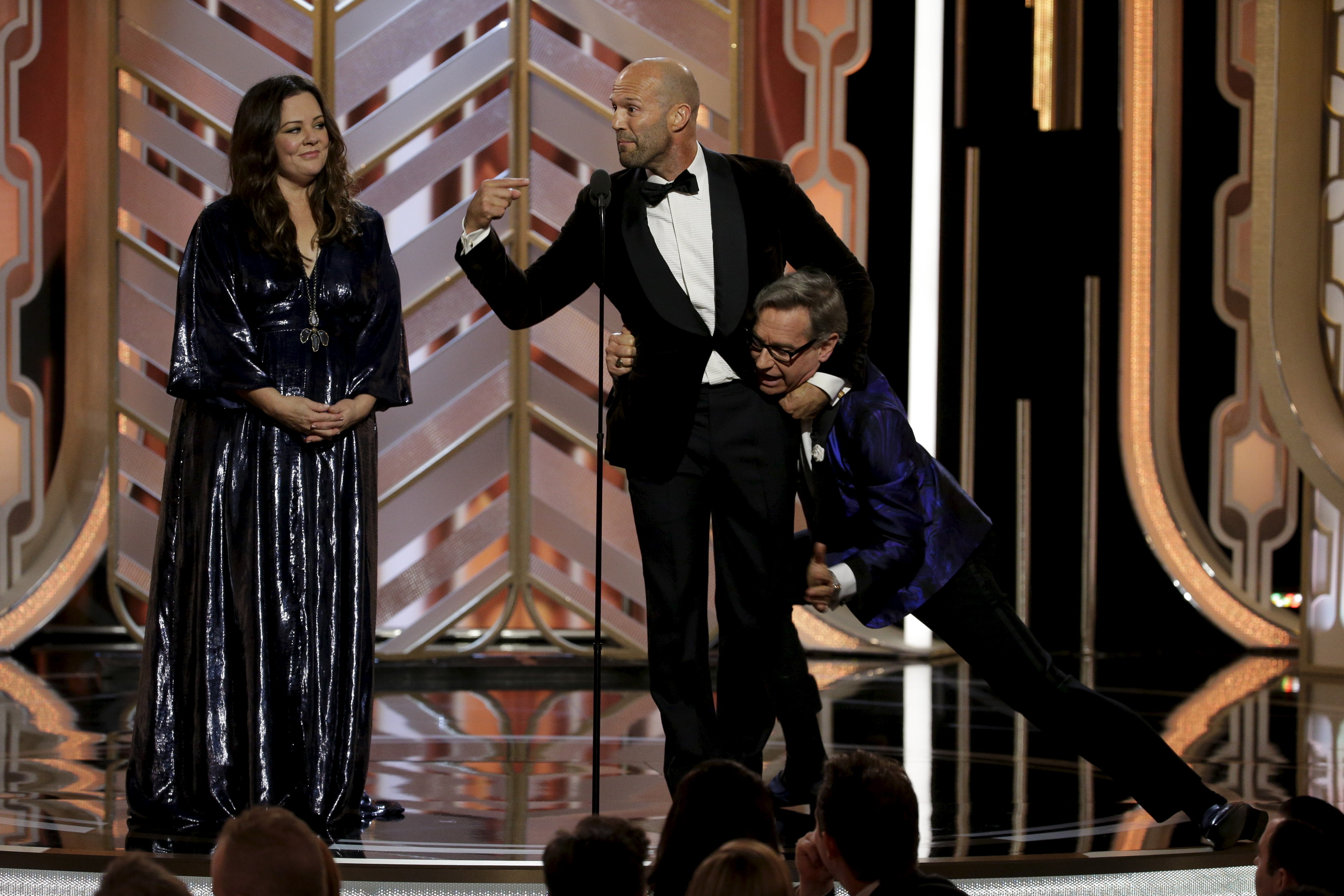 Melissa McCarthy (L) Jason Statham (C) and Paul Feig on stage at the 73rd Golden Globe Awards in Beverly Hills, California January 10, 2016. REUTERS/Paul Drinkwater/NBC Universal/Handout For editorial use only. Additional clearance required for commercial or promotional use. Contact your local office for assistance. Any commercial or promotional use of NBCUniversal content requires NBCUniversal's prior written consent. No book publishing without prior approval. - RTX21S66
