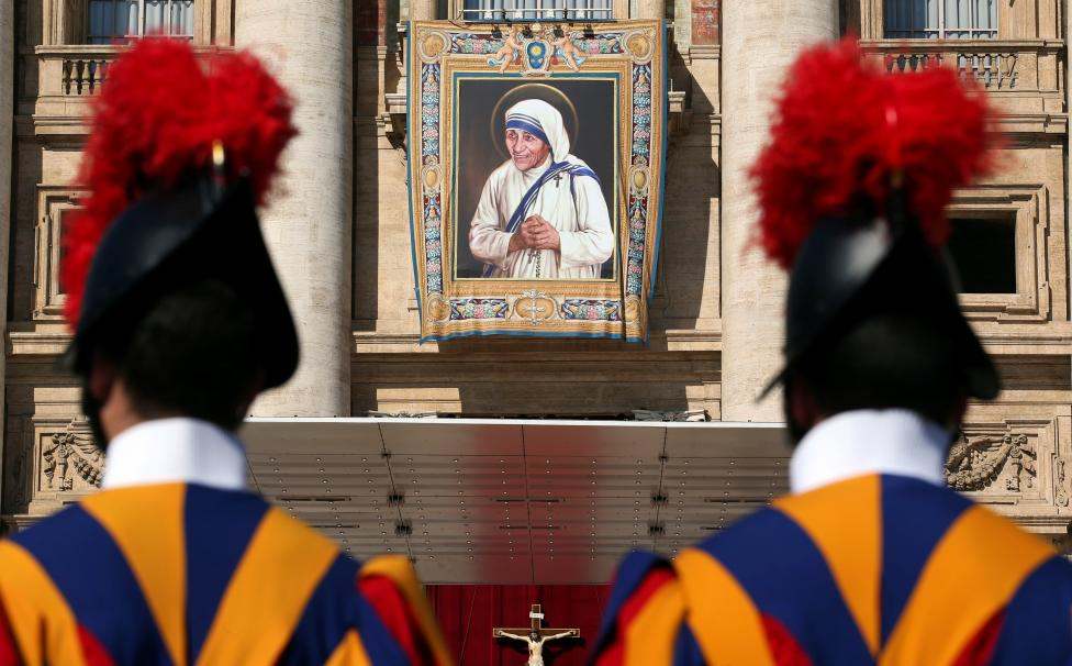 Swiss Guards stand in front of a tapestry depicting Mother Teresa of Calcutta before a mass, celebrated by Pope Francis, for her canonisation in Saint Peter's Square at the Vatican
